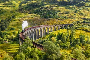 Glenfinnan Railway Viaduct in Scotland with a steam train